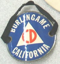 "Image of 1979.078 - WWII Burlingame Civil Defense Air Warden's armband, c. 1942-1945.  The armband is round and curved in shape and is made of brass along the edges with a glossy finish in the back. The armband has brass edges around the front of the armband, which has a blue background with some white bold painted text that reads ""BURLINGAME  /  CALIFORNIA"". In between the text ""BURLINGAME  /  CALIFORNIA"", there is a white triangle insignia with some orange bold painted text that reads ""CD"", which is the insignia for the United States Civil Defense Air Raid Warden. On the sides of the armband, there is a brass hole on each side with a black rubber strap that stitched and tied together in the back."