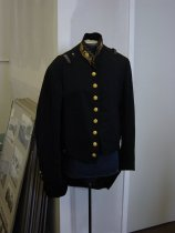 Image of 2008.048.001A - Captain William Matson Swedish Consul General Uniform, c. 1905-1917.  Black wool jacket with tails; 8 gold buttons decorated with Swedish crest on proper right side of front; 8 buttons across top of tails; 2 pocket flaps at back above tails; 4 smaller buttons at cuffs (1 gold, 3 pewter-colored, all with Swedish crest); collar embroidered with gold thread and gold beadwork in oak leaf and acorn motif; 2 embroidered straps at each shoulder to hold epaulets; beads form diagonal pattern; 2 metal clasps between collar and straps on each shoulder. Sleeves lined with white cotton with black striping.
