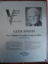 """Image of 2009.030.164 - Plaque commemorating Glen Smith of San Mateo County Parks and Rec being inducted into the San Mateo County Sports Hall of Fame on May 31, 1994.  Plaque includes image of Smith and a brief biography:  """"Glen Smith was a prime mover in the San Mateo County Parks and Recreation Department in the 1950s and '60s, helping to build the county's park system and recreation programs into the systems they are today.  /  He was responsible for parks like Butano, Huddart, Pescadero, San Bruno Mountain and Coyote Point, and programs such as Scouting, sports leagues, beach activities and offerings for seniors and the disabled.  /  He worked for the county for nearly 30 years and rose to chief of the recreation division.  He also played football and basketball at Jefferson High."""""""