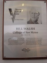 """Image of 2009.030.186 - Plaque commemorating Bill Walsh of College of San Mateo being inducted into the San Mateo County Sports Hall of Fame on May 18, 1993.  Plaque includes image of Walsh and a brief biography:  """"For Bill Walsh, the road from the College of San Mateo to the Superbowl was a long and varied one.  A former CSM quarterback for Coach Herb Hudson, Walsh graduated from San Jose State and then began his coaching career. He went from a high school job in the East Bay to assistant positions at Cal, Stanford and the Raiders, Bengals and Chargers of the NFL.  /  He did a first stint as Stanford's boss in 1977 and '78.  In 1979, he took over the Forty Niners top post, leading that NFL franchise to three Super Bowls.  He is a member of the Pro Football Hall of Fame.  /  He returned to Stanford in 1992.  The Cardinal tied for the Pac-10 championship that year.  In his two Stanford tours of duty, Walsh's teams have won three post-season bowl games in three tries."""""""