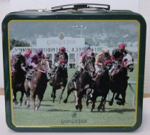 Image of 2010.013.001 - Dark green metal child's lunchbox with color photos of horse racing at Golden Gate Fields on one side and Bay Meadows on the other.  Racing shirt emblems surround sides along with logos of Golden Gate Fields and Bay Meadows.  Black plastic and metal articulated handle.  small flip lock in silver colored metal.