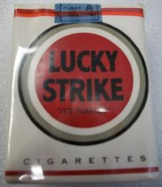 "Image of 2010.090.059 - Lucky Strike Cigarettes. c. 1939-1944.  Unopened.  Foil package covered with white paper with a red circle that says, ""LUCKY  /  STRIKE  /  'IT'S TOASTED'"" in black letters in center.  ""CIGARETTES"" is printed at bottom.  Blue paper seal at top.  All wrapped in clear celophane with a green stamp at the bottom."