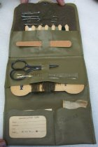 "Image of 2010.090.067 - WWII Military Sewing Kit. c. 1939-1944. Complete.  Guys would buy at PX in order to maintain their uniforms.  Green vinyl packet with black snap on front flap.  Contains four safety pins; four straight pins; cardboard thread holder with green, tan and white thread; one emery board; metal scissors; one clear plastic measuring rule; one cardboard thread holder with green wool; one glasine bag of buttons and one paper identification card.  Front flap says, ""MILITARY  /  Sewing Kit."""