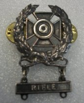 "Image of 2010.090.069 - WWII U.S. Army Sharpshooter Badge.  c. 1939-1944.  For rifle.  Pewter colored metal pin in the shape of a wreath with a cross in its center and a circular target in the center of the cross.  Bar hangs below wreath and says, ""RIFLE."""