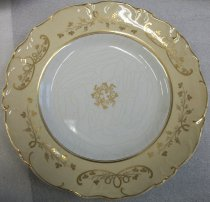 "Image of 2010.092.018B - Holbrook-Palmer Dinner Plate, mid-19th century.  One of a set of eight (2010.092.018A-H) mid-19th century French style dinner plates.  ""Improved Stone China"" stamped into back and ""2560"" written in red on back.  White plate with beige colored border and gold painted floral motif along border and in center.  Scalloped and textured edge."