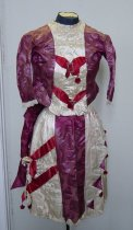 Image of 0002.114.001-002 - Silk Brocade Dress, 1885.  Silk brocade maroon 2-piece dress .001) top:  white satin inset with red satin ribbons and 2 silver buckles; lace on cuff; 12 silver buttons down back of dress; extra maroon panel down back and side of top; cream cotton lining  .002) Skirt:  maroon silk brocade with cream satin pleated sides and hem; trimmed with 4 red balls on left side and red ribbon, bows and red ball trim; 1 button closure; burlap lining.