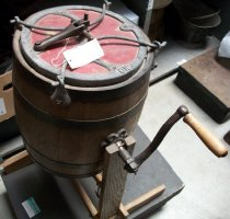 """Image of 0002.117 - Star Butter Churn, c. 1922-1927.  Barrel-type churn for making butter.  Wooden barrel with red wooden lid.  Lid is mounted with a black iron clamp.  Iron crank with wooden handle.  Unit is mounted to a wooden frame base for cranking.  """"Star"""" is written on both sides in black script.  """"OK"""" embossed on lid rim."""
