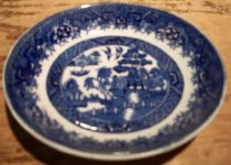 Image of 1999.054.001K - Semi China Sauce Plate, c. 1927-1950s.  White with cobalt blue Asian motif depicting birds, trees, a boat, building, bridge and fence.