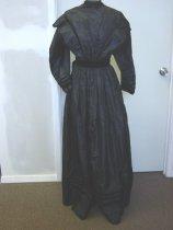 Image of 0002.295 - Black Taffeta Dress, c. 1890-1910.  Black taffeta dress, lined; black velvet trim at hem, shoulders, cuffs and belt; black lace at neckline; 8 buttons down front; dress closure with hooks and eyes