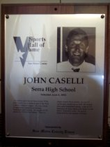 """Image of 2009.030.036 - Plaque commemorating John Casselli of Serra High School being inducted into the San Mateo County Sports Hall of Fame on June 4, 2002.  Plaque includes image of Caselli and a brief biography:  """"As a three-sport star at Serra in the 1970s, John Caselli was a marked man in the West Catholic Athletic League. He was a focus of opponents' attention in football, basketball, and baseball. He caught 16 TD passes in 1974 for the Padres. That is a single-season Serra record. He had 87 career pass receptions as well. He scored 843 career basketball points. Later at UC- Berkeley, he was a three-year starter on the Bears' basketball team. He played basketball for one season in Europe."""""""