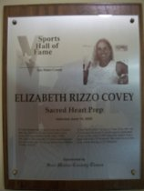 "Image of 2009.030.047 - Wood and acrylic plaque commemorating Elizabeth Rizzo Covey of Sacred Heart Prep who was inducted into the San Mateo County Sports Hall of Fame on June 19, 2008.  Plaque includes image of Rizzo Covey and a brief biography:  ""If long-distance shooting is your cup of basketball tea, Elizabeth Rizzo Covey had to be at the focus of your attention in the early 1990s.  She was in the vanguard of what would become the dominant girls' hoops program in San Mateo County History.  A four-sport athlete at Sacred Heart Prep, she was California's Division V (small school) basketball player of the year in 1993 when the Gators won a state title with a 37-0 record. She went on to a four-year career playing at UC-Berkeley."""