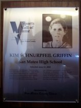 "Image of 2009.030.081 - Wood and acrylic plaque commemorating Kim Schnurpfeil-Griffin of San Mateo High School who was inducted into the San Mateo County Sports Hall of Fame on June 23, 2005.  Plaque includes image of  Schnurpfeil-Griffin and a brief biography:  ""Determination and dedication. That describes Kim Schnurpfeil Griffin to a tee. In the 1970's at San Mateo High School, she latched onto long-distance running when a coach spotted her potential in a conditioning class. She thrived in that discipline, becoming a Northern California cross-country champion in the process. At Stanford University, she as an all-American and NCAA champion in a variety of distance races. Today, she is a physician working in the critical care unit at a New York hospital."""