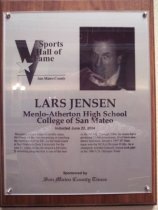 "Image of 2009.030.090 - Wood and acrylic plaque commemorating Lars Jensen of Menlo-Atherton High School and College of San Mateo who was inducted into the San Mateo County Sports Hall of Fame on June 22, 2004.  Plaque includes image of  Jensen and a brief biography:  ""Wrestling is Lars Jensen's middle name. He's been on the mat competing or coaching the sport most of his life. As the head coach at San Francisco State University for the past 21 years, he has developed a Division II wrestling program that is one of the best in the NCAA. Through 2004, his teams have produced 72 All-Americans, 24 of them academic honorees. Jensen's 1997 SF State team won the Division II title. As a champion wrestler himself, Jensen took part in the 1980 U.S. Olympic Trials."""