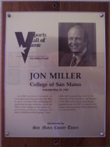 """Image of 2009.030.123 - Wood and acrylic plaque commemorating Jon Miller of the College of San Mateo who was inducted into the San Mateo County Sports Hall of Fame on May 22, 1997.  Plaque includes image of Miller and a brief biography:  """"Jon Miller was born to broadcast. As a youngster growing up in the East Bay, he spent countless hours practicing his sports play-by-play technique. In the late 1960's at the College of San Mateo, he got his first real chance, working on the mike at Bulldog football games. Late, Miller did broadcasting work for the University of San Francisco, the Warriors of the NBA and several major league baseball teams. In 1997, he became the Giants' lead announcer while continuing to work for ESPN."""""""