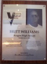 "Image of 2009.030.190 - Wood and acrylic plaque commemorating Britt Williams of Aragon High School who was inducted into the San Mateo County Sports Hall of Fame on June 22, 2004.  Plaque includes image of Williams and a brief biography; ""One of the most successful prep football coaches in San Mateo County history, Britt Williams has become an institution at Aragon High School. He arrived on that campus in 1968. He was the school's head football coach for 21 seasons, producing an overall 156-65-5 record in the process. That included six league titles and two Central Coast Section crowns. As a player at the University of Southern California, Williams was an honorable mention All-American in his senior year."""