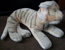 Image of 2010.147.002 - Steiff tiger given to Tom Petersen by his grandfather, George Coleman, who won it as a consolation prize at the California Golf Club in South San Francisco.  Light tan Steiff tiger with printed black stripes and orange highlights.  White fur around chin, cheeks and ears.  Yellow plastic eyes.  Tiger has embroidered mouth (black) and nose (orange).  Black paw prints are printed onto pads of feet.
