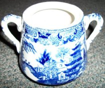 Image of 1999.054.002X - Sugar Bowl, c. 1927-1950s.  Blue and white Semi-China sugar bowl with no lid (missing?).  Bowl has a large base that tapers vertically and two small handles on either side.  Blue print depicts Asian motif that includes buildings, trees and a bridge.