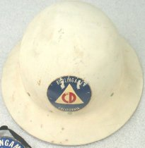 "Image of 1976.085.003 - Air Raid Warden's Helmet (WWII), c. 1914-1918. This metal helmet is round in shape and is painted in gray. In front of the top center portion of the helmet's head, there is a blue circle with a a triangle with a red symbol resembling some wings over four long round shapes, which is the symbol for Civil Defense Medical. On the back of the helmet on the inside border, it is surrounded by white metal bracket ends with holes connecting to small brass knobs with a brass wire bent on each. The brass knobs are tied to the brown leather head adjustment with a yellow cloth fabric stitched underneath. The brown leather head adjustment has four silver holes towards the back of the helmet that is tied together with brown shoelaces made of fabric. On the left and right side of the back of the helmet, there are two metal brackets painted in white tied to metal loops on each side that are tied the yellow fabric chinstrap in the middle that goes around the brown leather head adjustment. Part of the yellow chinstrap has a metal loop bracket to adjust the chinstrap. In the top middle of the back of the helmet, in a white and blue circle, above a big ""V"", printed in blue and bold, the text reads ""VICTORY  /  HELMET  /  BAILEY  /  HAT CO.  /  L.A."". On the outside border of the left side back of the helmet, engraved in bold, the text reads ""S S F"", with the words ""S S F"" is spaced out. On the outside border of the right side of the back of the helmet, engraved in bold, the text reads ""F A 19"", with the words ""F A 19"" is spaced out."