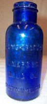 Image of 2006.254.007 - Cylindrical cobalt blue bottle with wide neck; lip same diameter as neck. Rim has 4 projections for metal cap closure.  Bottle is machine made.