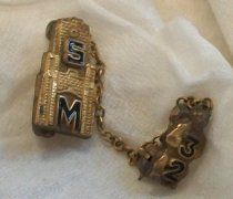 "Image of 2010.176.001 - San Mateo High School class pin from the class of '32.  Actually two gold colored pins connected by a small chain.  Larger pin has ""S M"" in black letters on front while smaller pin has the number ""32.""  Both pieces have a locking pin clasp on back."