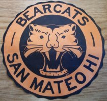 "Image of 2010.176.003 - Round paper Bearcats decal.  Orange paper has a mat finish on front side and a shiny surface on the back.  Bordered in a black scalloped edge the center has an orange tiger face on a black circle with the words ""BEARCATS  SAN MATEO HI"" surrounding it.  4 3/4"" diameter.  ""-BEARCATS-  /  SAN MATEO HI"" (black letters on front)"