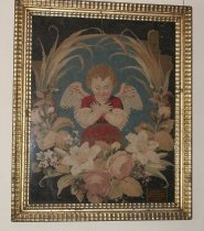 Image of 2015.033.001 - Little Angel Needlepoint by Hilaria Sanchez Reed, c. 1850.  Cloth needlepoint work under glass with gold wood frame.  Stitches include needlepoint, petipoint and one other in blue, red, brown, pink, and green on a black background depicting an angel with hands crossed over its chest surrounded by lillies, violets, roses and various leaves and grasses.  Angel is wearing red top and skirt with short sleeves, possibly edged in lace and has blond hair and white wings.  Frame is wood in covered in gesso and is painted gold.  It has a raised inner and outer border.  This was made by Hilaria Sanchez Reed who was a sister of Francisco Sanchez, c. 1850.