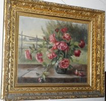 Image of 0002.312 - Tunitas Roses by Sybil Easterday, c. 1961.  Depicts a green vase full of red or pink roses.  Background is a landscape that includes a white building and a large tree.  Oil on canvas is mounted in an ornate wood and plaster frame that is painted gold.