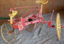 Image of RF2003.041 - P&O sulky plow.  This riding plow has a yellow metal seat which saved wear and tear on the body from walking on irregular soil but required more livestock to pull.  Solid iron, painted red with yellow iron spoked wheels:  a large one on left, small one on right in back behind blade and a medium-sized one in front of blade on right.  Large blade sits below to right and just in front of seat.  Levers on right and left allow adjustment of wheel height for blade placement.  Small oil can in meetal box on lower left side.