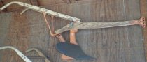 Image of RF2003.050 - Single Row Horse-Drawn Walking Plow.  Wooden hangles attach to wooden beam and center iron piece, painted orange, that holds blade.  V-shaped handle unit is mounted so that it can pivit from side to side.  Wood has clear laquer varnish.