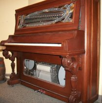 Image of 2008.067 - Coin Operated Stark Player Piano, c. 1922.  Upright player piano is solid wood with a brown stain finish.  Front panel above keys is stained glass with a clear beveled oval opening displaying an automatic xylophone.  It has three silver-colored metal foot petals.  The front panel above the foot pedals has a rectangular glass window displaying the piano music roll in the center and two drums on either side.  Piano is on casters and piano keyboard is supported by two legs, which are formed from ornately carved columns that are inscribed with geometric diamond, line, and fan motifs.  Top has a hinged door, which displays internal piano parts.  There is a light mounted beneath the top of door.  There is a decorative brass coin slot with twenty five cents and a hand with its finger pointed embossed on front; this is mounted in the top right corner of front panel.