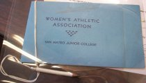 "Image of 2010.176.005 - San Mateo Junior College Women's Athletic Association Annual Banquet Program. Light blue cover. Front cover is one inch shorter in length than the back cover. ""M Campbell"" written on top of front cover in pencil. Dark blue text printed on cover. Miniature white pencil attached to program with white string.  ""M Campbell"" (written in pencil in cursive at top of cover); ""WOMEN'S ATHLETIC  /  ASSOCIATION  /  SAN MATEO JUNIOR COLLEGE"" (printed on cover)"