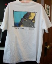 "Image of 2012.007.001 - One 1995 white cotton Hanes extra large T-shirt with a color cartoon image of Devil's Slide depicting a two-lane road going along the edge of a cliff.  Back has the words ""REPAIR"" and '""BYPASS"" with check boxes in front of them.  ""REPAIR"" is marked with an ""X."""