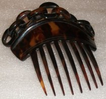 Image of 0002.227.001 - Tortoise Shell Comb, c. 1800.  Tortoise shell comb is translucent brown and orange and has eight tines below an arched horizontal piece with flared edges.  Attached above the top are nine oval-shaped links of chain carved from the same material.