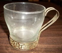 Image of 1973.322.001 - Glass coffee cup is narrow at the bottom and flares out toward top. It rests inside a gold-colored metal rim from which a handle extends up one side. Handle has two vertical open sections. Metal rim has a geometric openwork motif.