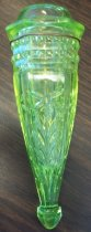 Image of 1977.264 - Carriage Vase, c. 1927.  Vase is made of yellow-green glass. Is cylindrical in shape and tapers to a point, then expands to form a pyramid shape with a rounded tip at the very base of the vase. Cross-section is hexagonal in shape with rounded corners. An embossed floral motif featuring a flower with six petals and eight leaves is on each of the four wider sides. A series of embossed dots decorate the thin sides of the hexagon. There is an incised slit going across three sides of the hexagon above the flower, probably to help secure it. Above the flowers are two bands of embossed squares decorating the top. Above the bands is a raised, plain band. Between the square bands and the plain one is an oxidized piece of metal wire twisted around the body of the vase (probably used to secure it). Beyond the plain band is the opening of the vase. Opening is round in cross section and  has the shape of a short cylinder which tapers slightly to a curved lip.