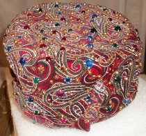 Image of 1986.158.001 - Beaded Paisley Toque, 1960s. Beaded paisley toque (women's hat) is made of red velvet with a paisley print in blue, green gold and white.  Hat is covered in gold metal beads and pink, blue, green and red plastic beads throughout.  Hat is lined with black taffeta.  It has a flat top and straight sides.  There is a small brim in the front and a velvet knot or bow made of the same paisley print at proper right side of brim.