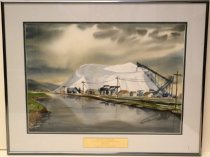 "Image of 1987.042.006 - 1986 The Salt Pile Watercolor by Robert Price.  Watercolor on paper is mounted in a white mat with a green inner border under glass in a gray metal frame.  Image depicts a salt pile in the background and water in the foreground with a gray cloudy sky above.  There are small buildings, telephone lines and cranes in front of the salt pile and reflected in the water.  Front of frame has a gold-colored metal plaque that says, ""FRED GELLERT FOUNDATION  /  COLLECTION OF SAN MATEO COUNTY SCENES  /  ROBERT PRICE  /  THE SALT PILE  /  PRESENTED BY ART-RISE 1986."""
