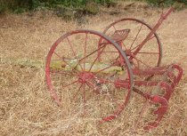 Image of RF2003.046 - Painted red iron metal morning mlory cutter with painted long yellow wooden beam out front.  Large twelve-spoke metal wheels on sides affixed to iron axle mounted to think horizontal wooden beam, painted red.  Spade-shaped seat with single row of oval perforations mounted above where wooden beams intersect.  Extending behind beam are four c-shaped pieces mounted to horizontal bars and used for popping out weeds.  A wire spring vertical lever is mounted to a D-shaped metal piece with round perforations along outer edge, right of seat and is used for adjusting wheel height.
