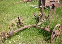 Image of RF2003.084 - John Deere disk plow.  Solid iron sulky (seated) disk plow has three wheels: one on left and two on either side of blade on right.  Beam out front is solid iron with a serpentine shape and a metal harness in front.  Seat is spade-shaped with two rows of oval-shaped perforations along outside edge.  Blade is a large round disk with a smaller blade in front top center of it for pushing dirt back down to form rows.  Tall lever just right of seat has a clamp at tapered handle that is attached to a rod, and a spring on the other side and moving notched piece at bottom that slides into one of the many notches of the stationary notched disk just left bottom of lever and is used for making adjustments to blade.  Two smaller similar lever, without springs, extend toward seat from front wheels and are used to make wheel height adjustments.