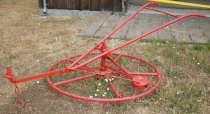 Image of RF2007.080 - Solid iron metal wheel cultivator or rotary harrow is painted red.  Wheel-shaped walking harrow has five-spoke horizontal wheel with spikes hanging below outer wheel and spokes.  Unit spins on vertical rod to which V-shaped handles with curved grips are mounted.  Point of handles attached to meter bar that extends out front.  There is a large rounded metal piece extending left and below handles. This type of cultivator is especially useful in orchards because it clears weeds without getting caught around tree trunks.