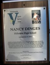 "Image of 2012.009.001 - Nancy Dinges Peninsula Sports Hall of Fame Plaque. Plaque commemorating Nancy Dinges of Hillsdale High School being inducted into Peninsula Sports Hall of Fame, sponsored by The San Mateo County/ Silicon Valley Convention and Visitors Bureau, on June 13, 2012. Plaque includes image of Dinges and a brief biography:  ""Whether as a shooter, ball-handler or passer, she was the well-tuned engine that made the Hillsdale girls' basketball machine hum in the late 1990s. She set a Peninsula Athletic League record for the most three-point shots made during her prep career. Then, at the University of the Pacific in Stockton, it was more of the same. During her four-year career with the Tigers, she set records for long-distance shooting. As of 2012, she was No.2 on the UOP three-point shooting list with 250 treys made. She was 11th in all-time Tiger scoring with 1,195 points. Her floor leadership and savvy later translated into a prep basketball coaching career."" Plaque is wood with an acrylic label attached to front with four screws, one in each corner. Wood has a hole in center top, as well as two grooves on back (one on the left and one on top below the hole), for mounting."