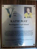 "Image of 2012.009.005 - Katie May Peninsula Sports Hall of Fame Plaque. Plaque commemorating Katie May of Burlingame High School being inducted into Peninsula Sports Hall of Fame, sponsored by The San Mateo County/ Silicon Valley Convention and Visitors Bureau, on June 13, 2012. Plaque includes image of May and a brief biography:  ""In the mid-1990s, she was a three-sport standout at Burlingame. But her softball prowess proved to be her greatest strength. She was a four-year starter for the Panthers as a shortstop and, after graduating, didn't miss a beat at U.C. Berkeley. Playing for the Golden Bears, she became the program's starting shortstop almost immediately. She was a smooth fixture and a fluid defensive standout at that position for four productive seasons, finishing her career with 596 assists, an all-time Cal record. Her team won 163 games and played in the College World Series twice. At the plate, she led the team with 12 doubles in 1998."" Plaque is wood with an acrylic label attached to front with four screws, one in each corner. Wood has a hole in center top, as well as two grooves on back (one on the left and one on top below the hole), for mounting."