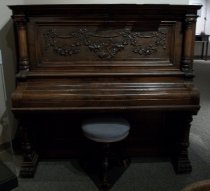 Image of 2012.011.001 - B. Shoninger Cabinet Grand Piano, 1857.  Serial #22101, New Haven, NH is a wooden upright piano decorated with floral carvings on front, sides, and legs. Front design also has a harp and trumpet, crossing over each other, among the flowers. The flowers are strung along ribbons with bows. Fluted columns on front side corners at top and bottom. Claw foot feet in front. Hinged key cover. Keys are a bit chipped and one black key is missing. Top has hinged opening as well.