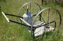 Image of RF2005.004 - Small milk cart used for transporting milk from the milking shed to the storage cellar.  Has large ten-spoke black painted iron metal wheels, a four-plank wooden platform and a horizontal wooden handle with tapered grips mounted to cart and wheels via black painted flat iron metal brackets.  There is an angled wooden crosspiece at base of handle side supports and about twelve inches above platform.  Displayed with old galvanized milk can found on Runnymede farm that has not yet been accessioned.