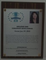 "Image of 2013.025.002 - 2013 Selena Ho Sports Hall of Fame Plaque.  Wood and acrylic plaque commemorating Selena Ho of Carlmont High School who was inducted into the Peninsula Sports Hall of Fame on June 11, 2013.  Plaque includes image of Ho and a brief biography:  ""One of the most prolific three-point shooters of her generation, she set basketball records at Carlmont High School and then took her considerable offensive skills to the University of the Pacific.  Her long-distance shooting prowess generated more statistical highlights at the collegiate level.  She ended her UOP career as the all-time Big West Conference leader in treys with 271.  She is third all-time in scoring at UOP with1,651 points.  She led the Tigers to the 2002 Big West Tournament title.  She was an all-Big West selection for four years."" Plaque and induction was sponsored by The San Mateo County/Silicon Valley Convention and Visitors Bureau in cooperation with San Mateo County Event Center and Media Sponsor The San Mateo County Times. Silver-colored plaque is mounted under acrylic onto a laminated wooden board by four decorative brass-colored screws and washers. Color image of Ho is in the upper right hand corner and Hall of Fame logo is in the upper left corner."