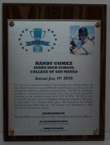"""Image of 2013.025.010 - 2013 Randy Gomez Sports Hall of Fame Plaque.  Wood and acrylic plaque commemorating Randy Gomez of Serra High School and College of San Mateo who was inducted into the Peninsula Sports Hall of Fame on June 11, 2013.  Plaque includes image of Gomez and a brief biography:  """"For a lesson in sporting reinvention, look no further than Randy Gomez.  At Serra High School, he was an all-WCAL baseball player; in addition, he was all-league in football as a defensive back/linebacker.  At CSM, he switched to quarterback, leading the league in passing.  Later, at the University of Utah, he wound up as the tenth-best passer in the U.S. in 1978.  He led an epic second-half comeback against rival Brigham Young, throwing three TD passes as Utah pulled off a stunning 33-32 upset.  He returned to the baseball diamond and hit .398 for the Utes.  His baseball career culminated in a 1984 stint with the San Francisco Giants."""" Plaque and induction was sponsored by The San Mateo County/Silicon Valley Convention and Visitors Bureau in cooperation with San Mateo County Event Center and Media Sponsor The San Mateo County Times. Silver-colored plaque is mounted under acrylic onto a laminated wooden board by four decorative brass-colored screws and washers.  Color image of Gomez is in the upper right hand corner and Hall of Fame logo is in the upper left corner."""