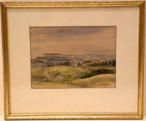 Image of 0001.606 - Burlingame Hills by W.C.F. Gillam, 1923.  Small watercolor on paper mounted behind a white mat under glass inside a gold-colored painted wooden frame with a recessed inner border and beaded outer border.  Image is from the perspective of the top of hills.  There is a row of trees in the background and a gray road and brown fence toward the center.  Image blurs as it goes out but it appears as if one is overlooking a town or city.  Top half of painting is comprised of gray and blue sky.