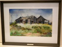 Image of 1973.186 - Chinese Shacks and Vegetable Gardens at Pescadero by H. Dodge.  Watercolor on paper mounted behind glass and a white mat board inside a brown wooden frame.  Image depicts gray-brown-colored buildings in the background with a field of greens browns and golds, some of which is in rows, in the foreground.  There are telephone lines behind the buildings on the left and there is a blue and white sky above.