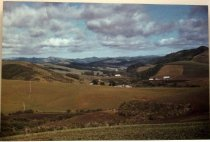 Image of 1986.327.004 - 1985 San Gregorio from Old Stage Road by Frank Spadarella.  Color photograph mounted to a masonite wooden board.  Image depicts fields of farmland scattered with a few barns and other buildings.  There are hills in the distance and clouds in the sky.