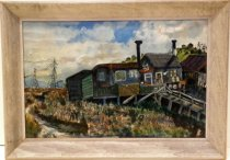 Image of 1989.352 - Shanty Town by Ruth Garber Hulstede.  Oil painting in a gray colored wooden frame.  Image depicts a field and, possibly, a creek in the foreground with green, blue red and white buildings in the center right.  There is a raised boardwalk extending from right of image to blue building with two chimneys.  Buildings are set against a green hillside and there are power lines in the field to the left.